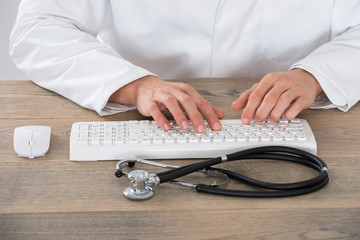 Male Doctor Typing On Computer Keyboard