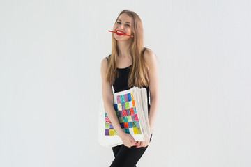 Front view portrait of young female artist holding the hand drawn pictures pack, smiling with a pencil in her teeth.