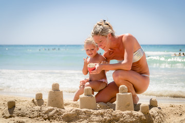 Wall Mural - Mom and daughter building a castle of sand on the beach.