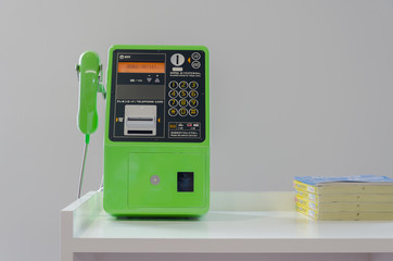Green publc telephone on table