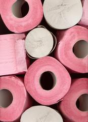 Pink toilet paper rolls closeup background