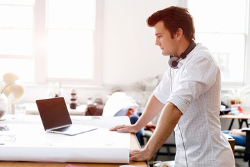 Young man standing in creative office