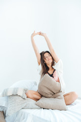 Relaxed woman sitting and stretching on bed