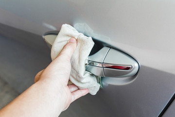 Cleaning car handle with chamois towel.