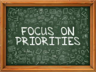 Focus on Priorities - Hand Drawn on Green Chalkboard with Doodle Icons Around. Modern Illustration with Doodle Design Style.