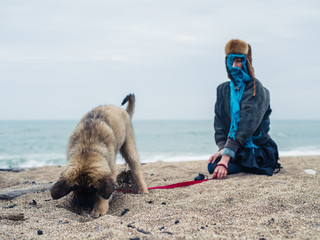 Woman on the beach with a young Leonberger puppy