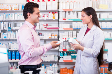 Pharmacist counseling customer about drugs
