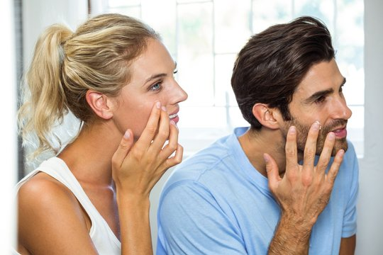 Man and woman applying moisturizer on their face