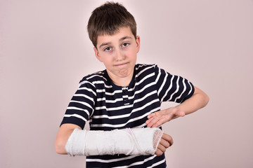 Young boy making a grimace and showing his broken arm with plaster