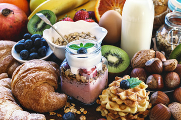 Health breakfast - with homemade granola, waffles, muffins,almond,hazelnuts,various fresh fruits, berries and milk on old wooden table. Health food concept .Top view.