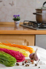 Multicolored pasta on a wooden table in the kitchen background