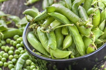 freshly picked organic peas on a rustic wooden table