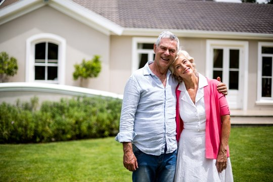 Senior couple with arms around standing in yard