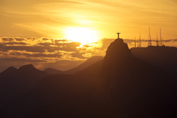 Corcovado mountain Christ the Redeemer standing in golden sunset clouds Rio de Janeiro Brazil