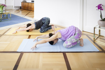 two women doing yoga at home Balasana variation