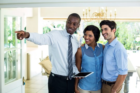 Real estate agent showing the house to couple