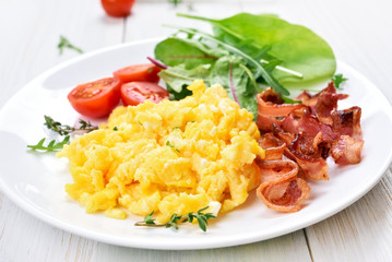 Scrambled eggs, bacon and vegetable salad