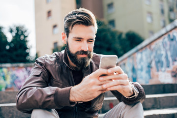young handsome bearded man using smartphone