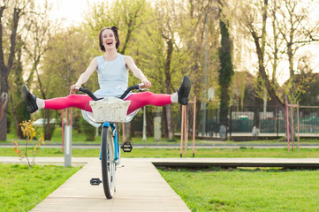 Cheerful woman riding bicycle with her legs in the air
