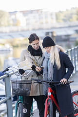 Women with bicycles looking at map in cell phone