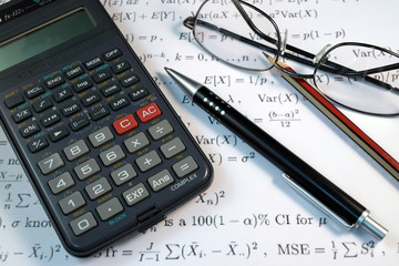 Eye Glasses, pen and pencil over the Formula with calculator