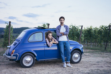 Young couple doing a road trip in Tuscany countryside in a vintage car