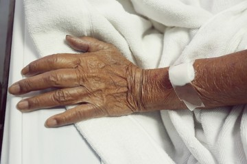 old woman's hand is on a drip receiving a saline solution.