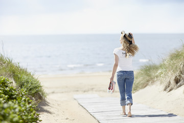 Young woman walking on beach with sea in background