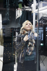 Woman trying on fur scarf in shop