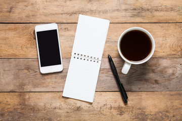 Top view White smart phone, note, pen, headphone and cup of coffee or tea on wooden background