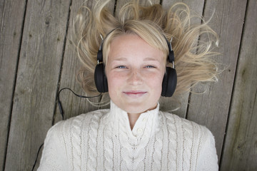 Portrait of blond girl lying on wooden pier and listening to music