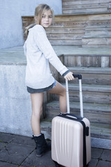 Portrait of blond girl with suitcase