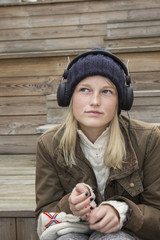 Blond girl sitting on steps and listening music