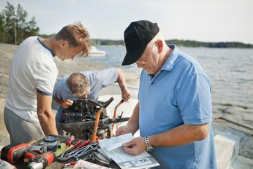 Men repairs boat engine