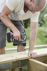 Mid-adult man drilling plank