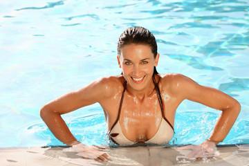 portrait de belle femme souriante à la piscine sortant de l'eau