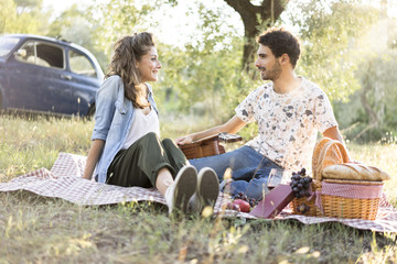 Young couple in love doing a picnic outdoors in Tuscany wine country