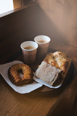 Fresh sweet bakery bread, two kraft cups of black coffee on a paper tray, wooden background. Coffee break concept. Breakfast in the sunny morning