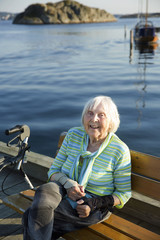 Smiling senior woman sitting at sea