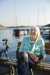 Smiling senior woman sitting at sea