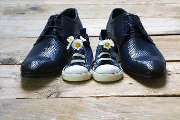 Father's day, kids sneakers with a bouquet of daisies and daddy's shoes