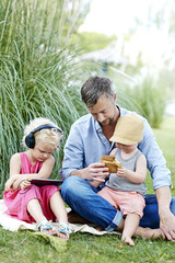 Father relaxing with children in garden