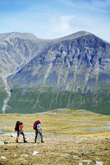 Female backpackers hiking in landscape