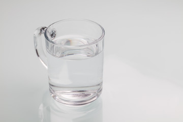 Drinking water isolated on gray background. Close-up studio phot