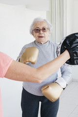 Senior woman boxing with fitness instructor