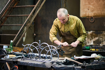 The blacksmith shapes the metal using a vise