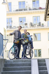Parents with son and bicycles by building