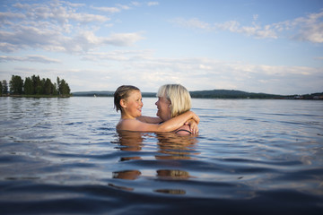 Mother and daughter swimming in lake