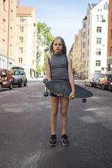 Girl standing in street, holding skateboard