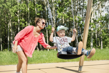 Mother swinging son on playground